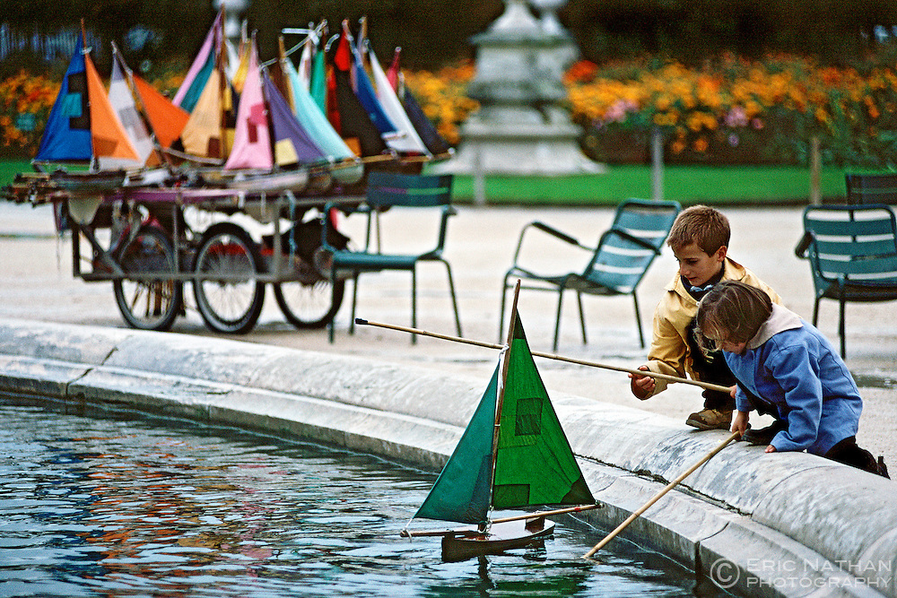 Children playiing with model sail boats on the pond in the Jardins des Tuilleries in Paris.