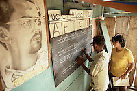 July 1980, Nicaragua --- A woman teaches a man how to print letters on a blackboard as part of a literacy program. They stand next to a painting of a man with La revolucion written beneath. --- Image by © Owen Franken/CORBIS - Photograph by Owen Franken