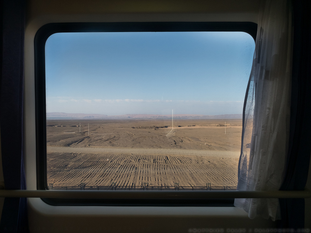 Coming down from the tibetan plateau,  reaching the edge of the Taklamakan desert near Urumchi. This is the Turfan depression, located entirely below sea level and also the hottest and driest area in China. Window view across China, from Hong Kong to Urumqi, Xinjiang.