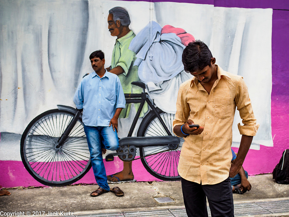 """09 JULY 2017 - SINGAPORE: Guest workers from the Indian sub-continent in front of a mural in Singapore. There are hundreds of thousands of guest workers from the Indian sub-continent in Singapore. Most work 5 ½ to six days per week. On Sundays, the normal day off, they come into Singapore's """"Little India"""" neighborhood to eat, drink, send money home, go to doctors and dentists and socialize. Most of the workers live in dormitory style housing far from central Singapore and Sunday is the only day they have away from their job sites. Most work in blue collar fields, like construction or as laborers.    PHOTO BY JACK KURTZ"""