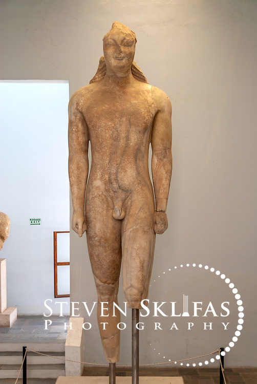 Greece. Samos. Front view of the gigantic Kouros on display at the Archaeological Museum in Vathy or Samos town. Found in 1980 to the east of the Heraion, the colossal 4.80 metres high Kouros dates from 580 BC and was built from a single piece of grey veined Samian marble. According to the inscription on its left thigh, the Kouros is dedicated to Goddess Hera by a certain person named Isches. The Kouros is the largest free standing sculpture to have survived from the ancient Greek world