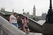 Wet young tourists and visitors to London's Southbank, endure heavy summer rainfall on the steps of Westminster Bridge, England.
