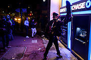 A demonstrator uses a skateboard to hit the Chase ATM at the intersection of 8th and Franklin streets in Oakland on Friday, May 29, 2020. Demonstrators gathered Friday night in Oakland to protest the death of Minneapolis man George Floyd.