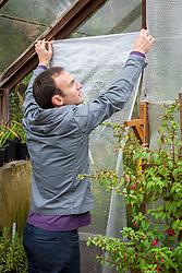Putting up greenhouse insulation (bubblewrap)