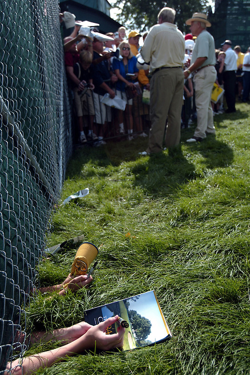 Hopeful , desparate and inventive fans without a pass to get into the PGA tournament try to get the attention of pro golfer John Daly on the opening day of the PGA at Hazeltine National Tournament in Chaska, MN. ....