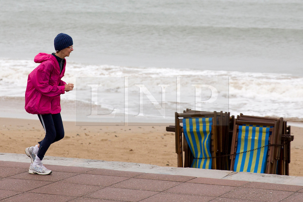 © London News Pictures. 02/06/2015. United Kingdom, Swanage. A runner wrapped up in cold weather. Grey skies cover the sky over a windy seafront at Swanage, Dorset, on June 2, 2015. Photo credit: LNP