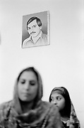 A woman beneath a portrait of her murdered husband, rabwah, Pakistan. Also known as Qadiani's The Ahmadiyyas are the followers of Hazrat Mirza Ghulam Ahmad Qadiani (1835-1908). According to his followers, he was the  founder of the Ahmadiyya Muslim Jama'at and The Promised Messiah and Imam Mahdi. The Ahmadiyya (Qadiani) movement in Islam is a religious organisation with more than 30 million members worldwide. Ahmadiyyas are now banned from calling themselves Muslim in Pakistan and suffer terrible discrimination under anti-blasphemy laws and are regularly murdered for their faith.