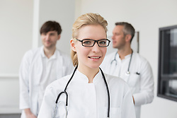 Female doctor, colleagues in background