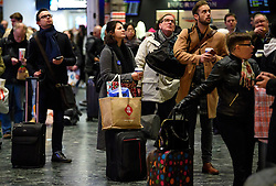 © Licensed to London News Pictures. 24/12/2016. London, UK. Festive holiday makers wait for their train at Euston Station in London on Christmas Eve, as the Christmas getaway continues, with stations, airports and roads expected to be very busy as people start their Christmas holidays. Photo credit: Ben Cawthra/LNP