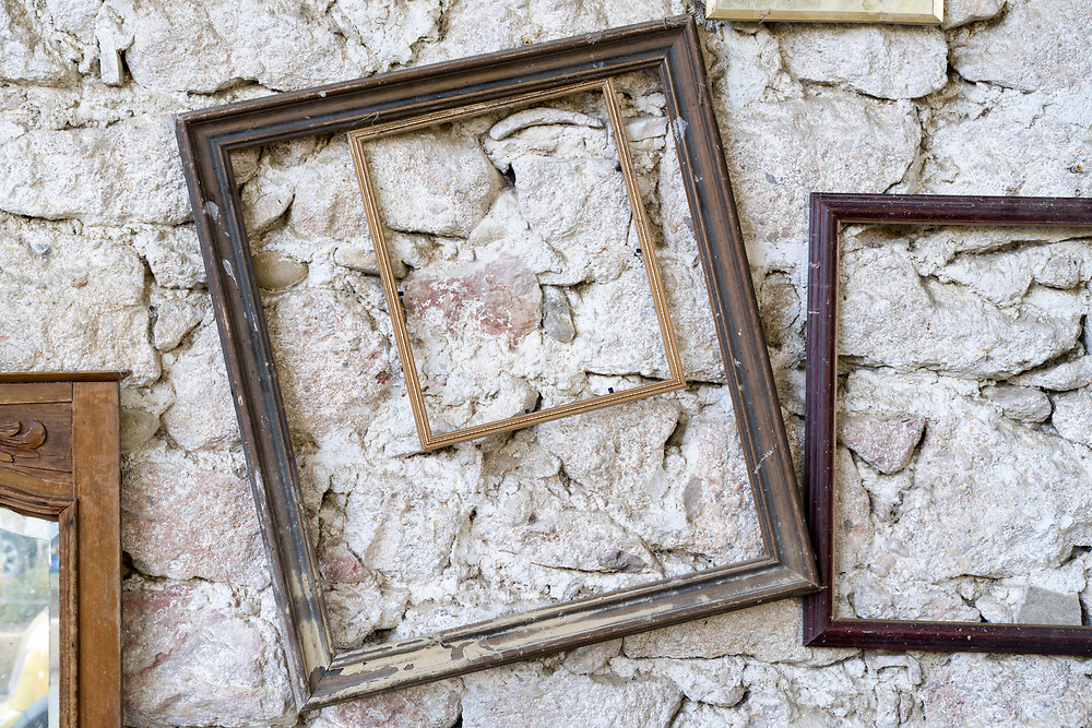 empty old picture frames agains rustic stone wall