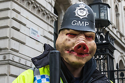 "London, April 16th 2016. A ""pig"" dressed as a policeman poses for the camera outside the gates of Downing Street as thousands of people supported by trade unions and other rights organisations demonstrate against the policies of the Tory government, including austerity and perceived favouring of ""the rich"" over ""the poor""."