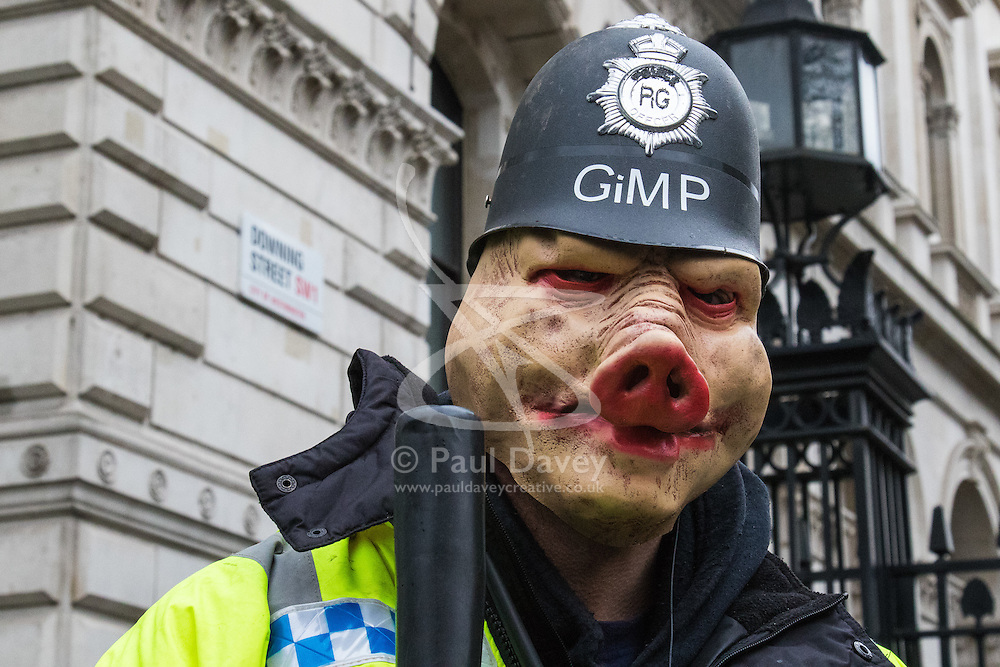 """London, April 16th 2016. A """"pig"""" dressed as a policeman poses for the camera outside the gates of Downing Street as thousands of people supported by trade unions and other rights organisations demonstrate against the policies of the Tory government, including austerity and perceived favouring of """"the rich"""" over """"the poor""""."""