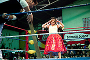 Alicia Flores female wrestler in headlock from male opponent, with crowd in background. Lucha Libre wrestling origniated in Mexico, but is popular in other latin Amercian countries, including in La Paz / El Alto, Bolivia. Male and female fighters participate in the theatrical staged fights to an adoring crowd of locals and foreigners alike.