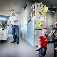 Nederland, Amsterdam , 7 juli 2010..Eberhard van der Laan thuis in zijn woning op de Baron G.A. Tindalplein 207, trekt de schoenen van zijn kinderen aan alvorens ze naar de creche worden gebracht..Vanmiddag, woensdag 7 juli, wordt de nieuwe burgemeester van Amsterdam geïnstalleerd. Eberhard van der Laan (55) zit de komende zes jaar op 'de mooiste stoel van de stad'..On the day of his inauguration as mayor of Amsterdam,Eberhard van der Laan is taking care of his children before they are brought to the creche.