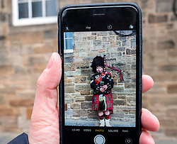 Tourist taking photo of Scottish man in tartan playing bagpipes on the Royal Mile in Edinburgh Old Town, Scotland, United Kingdom