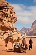 Women stand besides camels in Wadi Rum, Jordan.