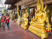 """12 NOVEMBER 2012 - BANGKOK, THAILAND:   People walk by Buddha statues for sale in a shop on Bamrung Muang Street in Bangkok. Thanon Bamrung Muang (Thanon is Thai for Road or Street) is Bangkok's """"Street of Many Buddhas."""" Like many ancient cities, Bangkok was once a city of artisan's neighborhoods and Bamrung Muang Road, near Bangkok's present day city hall, was once the street where all the country's Buddha statues were made. Now they made in factories on the edge of Bangkok, but Bamrung Muang Road is still where the statues are sold. Once an elephant trail, it was one of the first streets paved in Bangkok. It is the largest center of Buddhist supplies in Thailand. Not just statues but also monk's robes, candles, alms bowls, and pre-configured alms baskets are for sale along both sides of the street.    PHOTO BY JACK KURTZ"""