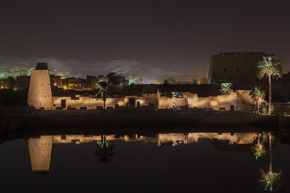 EGYPT. Luxor. December 26th, 2013. Karnak Temple reflected in the Sacred Lake with the Valley of the Kings in the distance across the nile river.