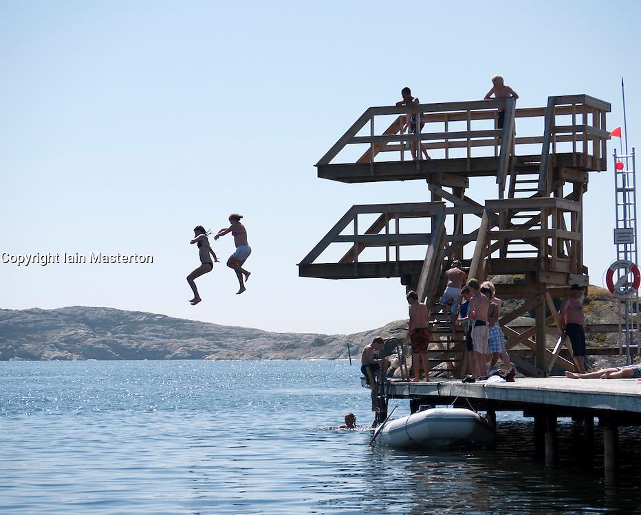 Children jumping from diving platforms into sea during summer at Skarhamn on Bohuslan coast in western Sweden