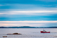 A colorful, red lobster boat out on the bay, the sky is striated horizontally, along with a horizontal rock formation and dinghy, all adding to the graphic effect of the image.