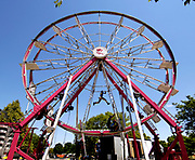 """Lenard """"Sarge"""" James swings from one side to the other as he and other workers set up the ferris wheel for the 2012 Eyes to the Skies festival in Lisle, Tuesday."""