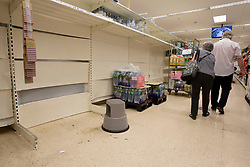 © Licensed to London News Pictures.  22/07/2021. London, UK. Shoppers walk past empty shelves in Tesco, Hackney, east London. Supermarkets have warned they could start running out of food in 48 hours. Many stores had to close due to a lack of workers having to self-isolate.  Photo credit: Marcin Nowak/LNP