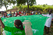 Nurse Agnes and fellow colleges from Bwindi Community Hospital give a demonstration of how to use a mosquito net during an outreach clinic in Kitahurira, the only Batwa tribe settlement in Mpungu district. Bwindi Community Hospital provides different outreach clinics everyday for the surrounding area around Buhoma. The Mpungu district is on the edge of the Bwindi Impenetrable Forest, Western Uganda.