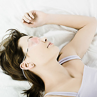 woman lying on a white bed wearing a cryogenic facial beauty treatment mask