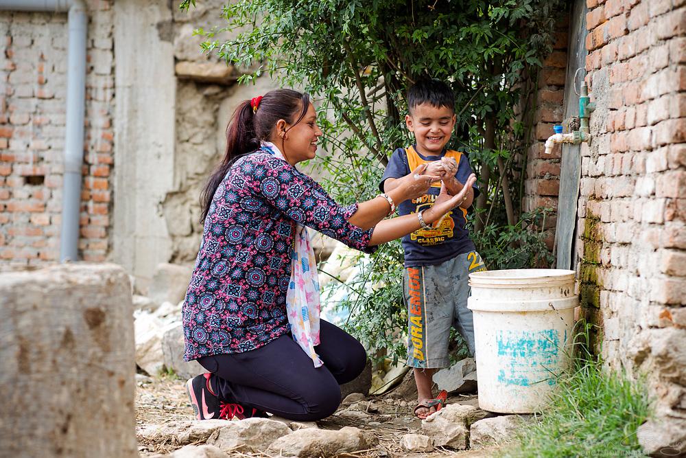 Local ENPHO staff member, Radhika Ghamire, teaching four year-old Rhythm Phuyal the technique for effective hand washing., Kakani, Nuwakot District, Nepal