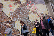 Shoppers walk beneath a world map on a bakery business hoarding. The group of women consumers pass beneath the large billboard screening off construction work for a new Turkish bagel business called Simit Sarayi that shows a world map made from dough with a dusted flour covering. Countries from America to Europe and the Middle-east show the locations of the business's presence around the globe. The women walk westwards towards Piccadilly Circus. Simit Sarayı started in 2002 with a single store. Today, with hundreds of stores in Turkey and abroad with 10.000 employees to over 650.000 daily visitors.