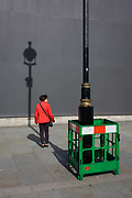 Lone woman with a lamp post shadow against a grey construction hoarding in central London's Trafalgar Square. Painting work is being carried out to the street lighting lamp post, a green plastic fence surrounding the wet paint while the post's upright has created a strong linear theme to the pavement and background hoarding that screens other work.