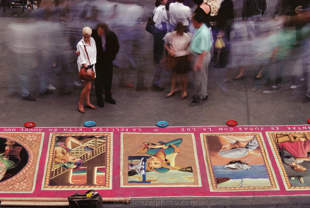 Passerbys examine sidewalk chalk art on Las Ramblas, Barcelona, Spain.