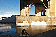 A couple on bicycles kissing under the 6th Street Bridge in downtown LA. The bridge is the scene of hundreds of movies, TV shows, and commercials..The bridge will be soon torn down and replaced.