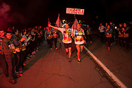 """A crowd of people welcomes  2 runners on the 20th Korrika. Cintruenigo (Basque Country). April 1, 2017. The """"Korrika"""" is a relay course, with a wooden baton that passes from hand to hand without interruption, organised every two years in a bid to promote the basque language. The Korrika runs over 11 days and 10 nights, crossing many Basque villages and cities. This year was the 20th edition and run more than 2500 Kilometres. Some people consider it an honour to carry the baton with the symbol of the Basques, """"buying"""" kilometres to support Basque language teaching. (Gari Garaialde / Bostok Photo)"""
