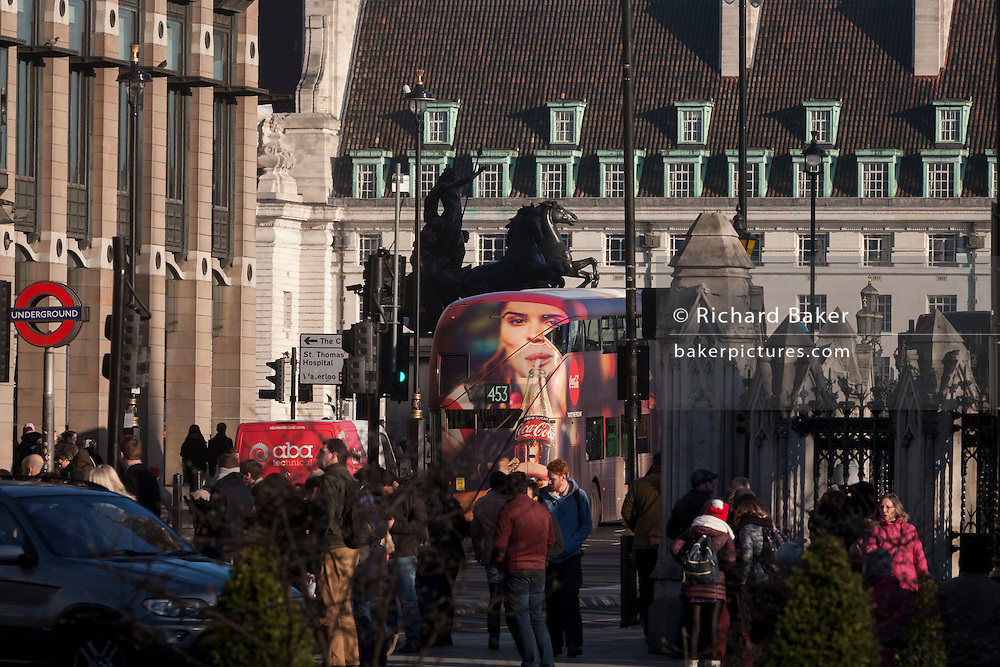A Coca-Cola ad appears on the rear of a London bus as it travels through Westminster, passing the tall statue of Iceni tribe leader Boudicca, on 18th January 2017, in Parliament Square, London England.