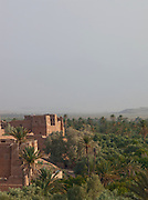 A kasbah towers over palms of the Skoura Oasis in Morocco