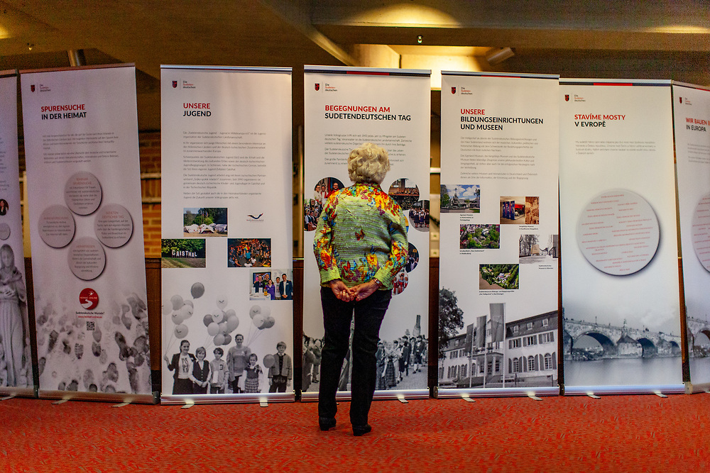 """A woman infront of an exhibition at the 71st Sudeten German meeting at the """"Philharmonie im Gasteig"""" in Munich."""