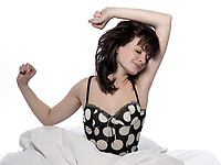 young woman in a white sheet bed on white  stretching