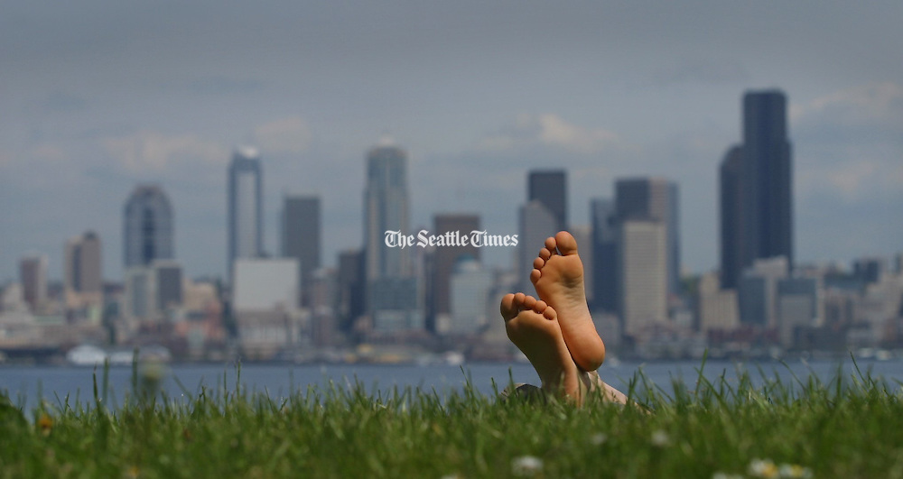 A sunbather relishes the warm sunshine at Alki in front of a backdrop of Seattle's skyline.<br /> (Ellen M. Banner / The Seattle Times)