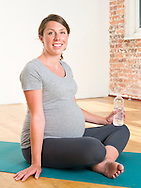 Pregnant woman (3rd trimester) sits on a yoga mat holding a bottle of water.