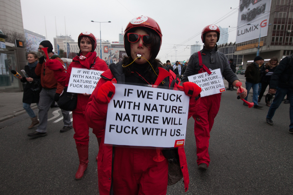 Protestors carry signs saying 'If we fuck with nature, nature will fuck with us' during march for Climate and Social Justice at COP19, UN climate change conference in Warsaw, Poland