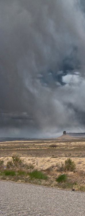 storm clouds drop streams of rain in the distance beyond mesas along highways US 491/US 160 in southwesten Colorado near the New Mexico state line.  panorama
