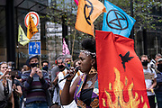 Speaker talks emotionally of the history of the exploitation on the Walk of Shame disruptive mach through the City of London by environmental group Extinction Rebellion on 4th September 2020 in London, United Kingdom. The walk visited various locations in the financial district, to protest against companies and institutions with historical links to the slave trade, or who finance or insure projects which are seen as ecologically unsound. The message by the group is that 'apologies and token attempts at diversity are not enough to address this legacy and present reality. Our demand is reparations and reparatory justice for those affected by colonial and neo-colonial exploitation'. Extinction Rebellion is a climate change group started in 2018 and has gained a huge following of people committed to peaceful protests. These protests are highlighting that the government is not doing enough to avoid catastrophic climate change and to demand the government take radical action to save the planet.