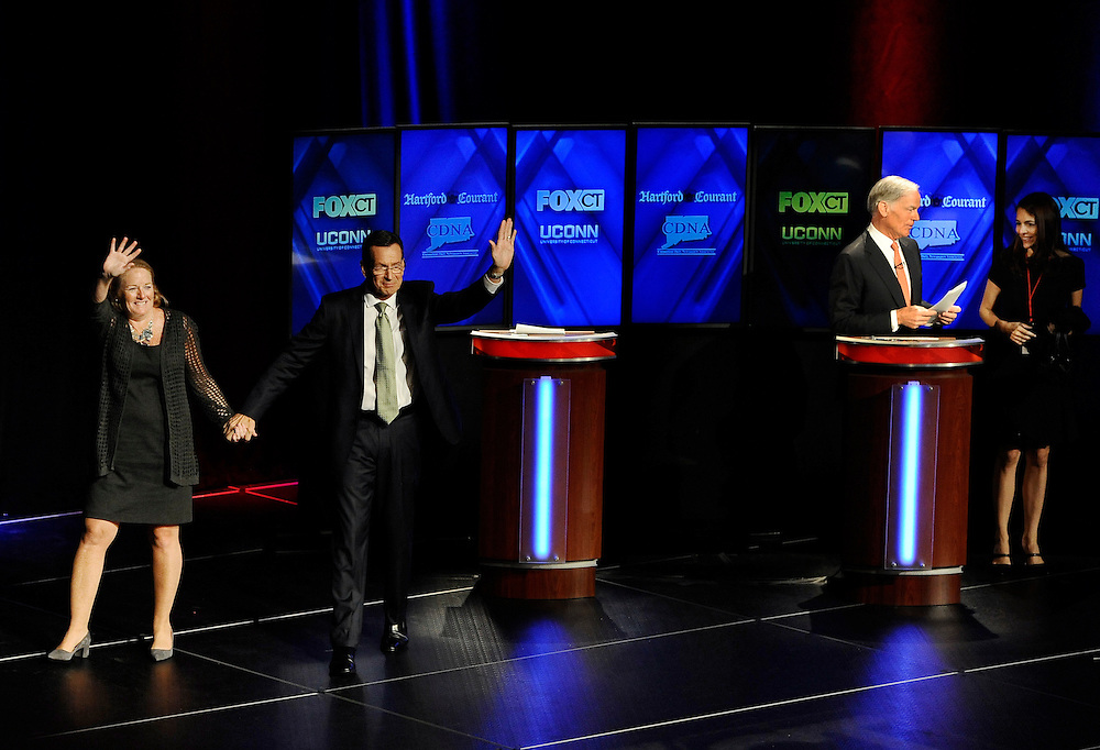 Incumbent Democrat Gov. Dannel P. Malloy, second from left, waves with wife Cathy, left, as Republican candidate for governor Tom Foley, second from right talks with his wife Leslie, right, speak to one another at the end of a debate at the University of Connecticut, Thursday, Oct. 2, 2014, in Storrs, Conn.  (AP Photo/Jessica Hill)