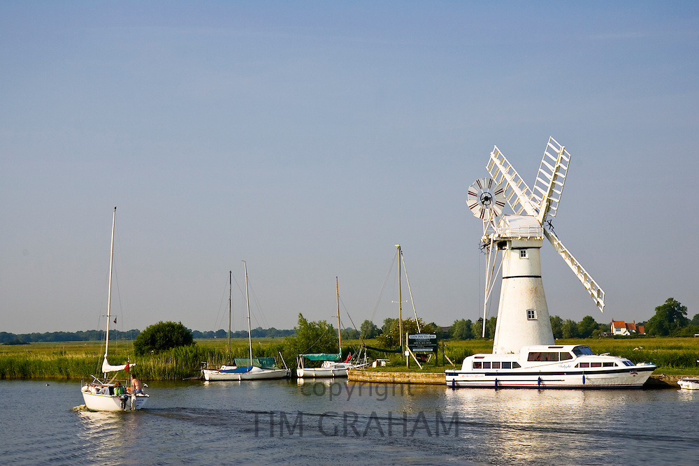 Sailing boats and river cruisers pass windmill on Norfolk Broads, United Kingdom