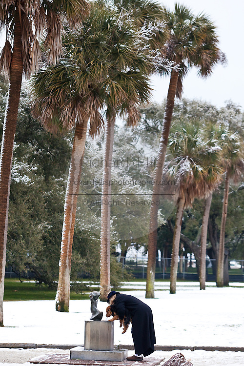 CHARLESTON, SC - February 13: A women pauses to give her dog a drink from the doggy fountain in snow covered White Point Gardens February 13, 2010 during a rare snow storm in Charleston, SC. About 3-inches of snow fell on the Charleston area, the first significant snow in 20-years.    (Photo Richard Ellis/Getty Images)