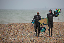 © Licensed to London News Pictures.  03/05/2021. Brighton, UK. Kite-surfers walk along cost line of Brighton Beach in East Sussex, following The May Day, bank holiday as forecasts predict strong winds and rain for the coming week. Photo credit: Marcin Nowak/LNP