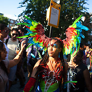 A young black woman dressed in feathers makes her way through the crowd. The Notting Hill Carnival has been running since 1966 and is every year attended by up to a million people. The carnival is a mix of amazing dance parades and street parties with a distinct Caribbean feel.