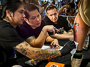 28 OCTOBER 2018 - BANGKOK, THAILAND: Judges score a man's tattooed leg during judging of the Next Generation division (for tattoo artists with less than 5 years experience) at the 2018 MBK Center Tattoo Fest. Tatoo artists from around the world came to participate in the festival, which featured both modern (using tattoo machines) and traditional methods (done by hand with long needles) of tattooing. PHOTO BY JACK KURTZ