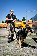 Reward treat in mouth, K-9 patrol dog Koda tugs his handler, Frank Bowne, on the way back to their squad car following a basic training exercise at the Post Falls District bus barn on Friday.